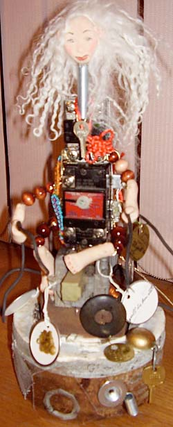 This is my latest creation. Her name is Burnt Out. She is made from a burnt out motor of a vacuum and other found stuff, clay and  lamb's wool for her hair.  I manage a janitorial service.....Sandy Briggs. Elkhart Indiana